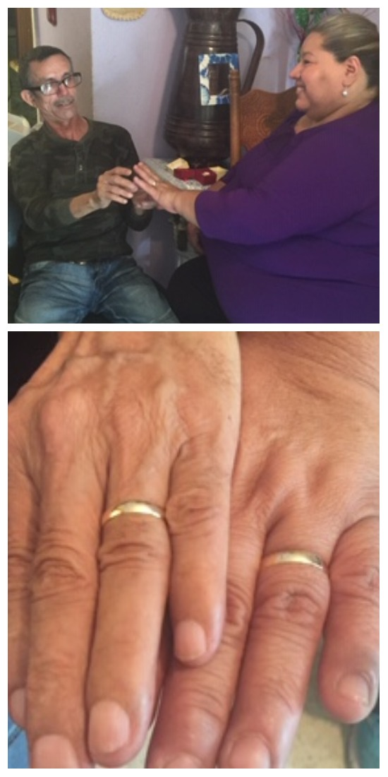 The couple places rings on each other's hands (above), and show off their wedding bands (below)