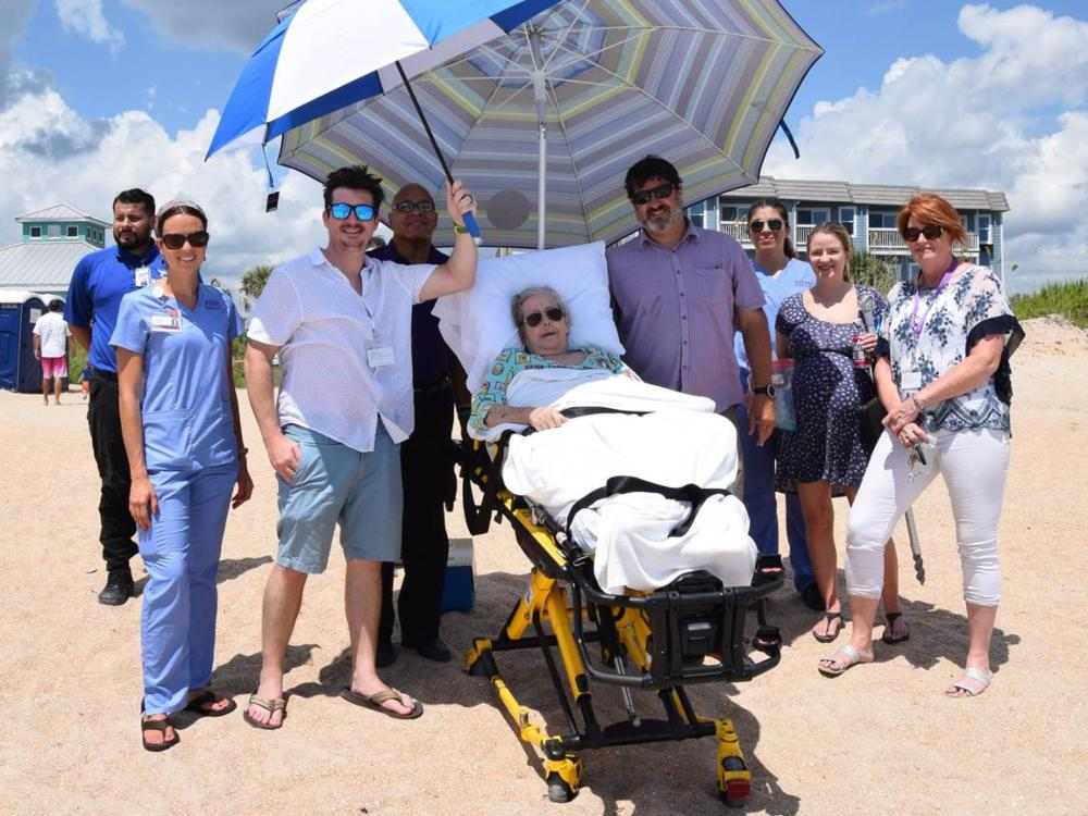 The team poses with Ms. Hands in her hospital bed at the beach, helping shelter her from the hot Florida sun with an umbrella