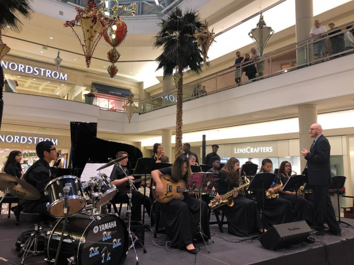 A group of students play guitar, saxophones, drums and other instruments on stage at the mall