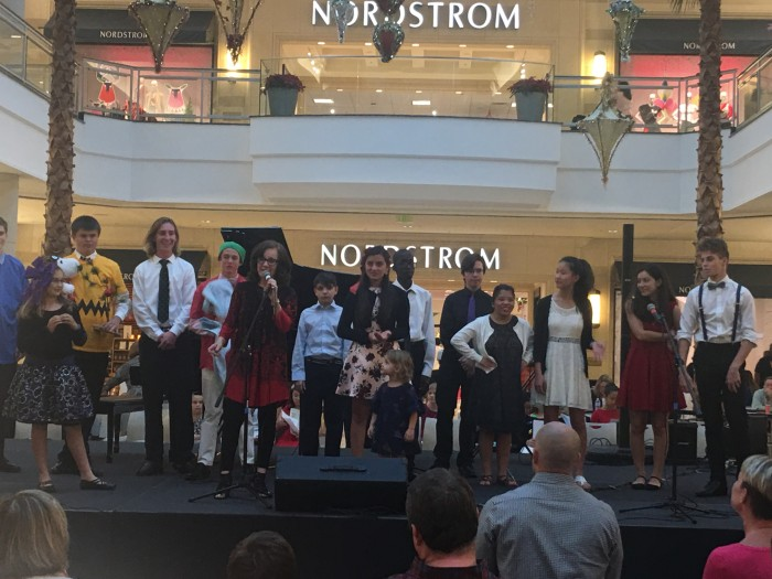 A group of young people on stage at the mall