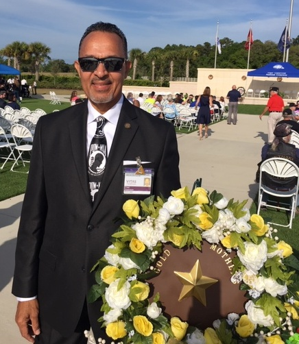 Fred Robinson stands next to a commemorative wreath
