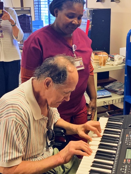 David plays his keyboard as a member of his VITAS hospice care team looks on