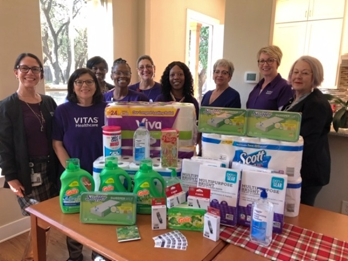The team with items they donated, including essentials like laundry detergent, paper towels, toilet paper and Swiffer sweepers