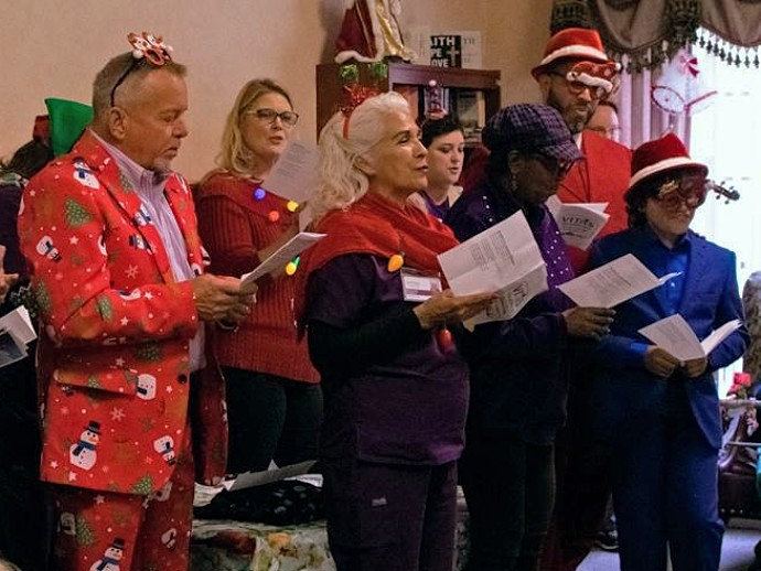 The carolers sing to a group at Senior Care Wurzbach