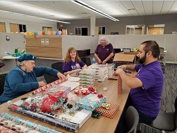 Volunteers wrapping gifts at CASA