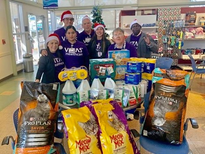 The team with pet food and other supplies they donated to the Humane Society