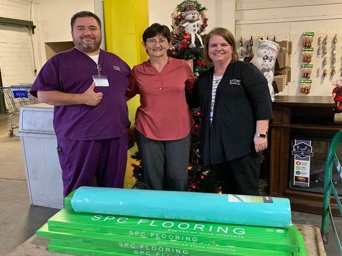 Three team members pose with the flooring materials they donated to Tended Treasures