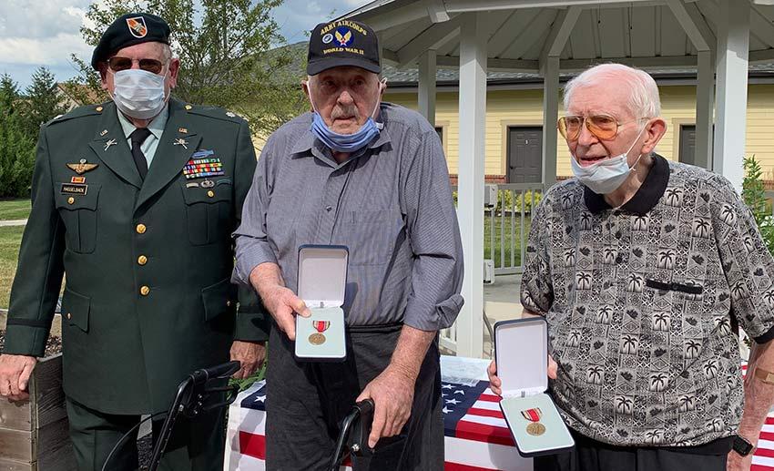 Dehlin y Fuller sostienen sus medallas y Hasselback observa