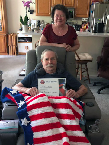 VITAS patient William Slack shows the certificate he received from VITAS, with his wife Roxanne standing behind him
