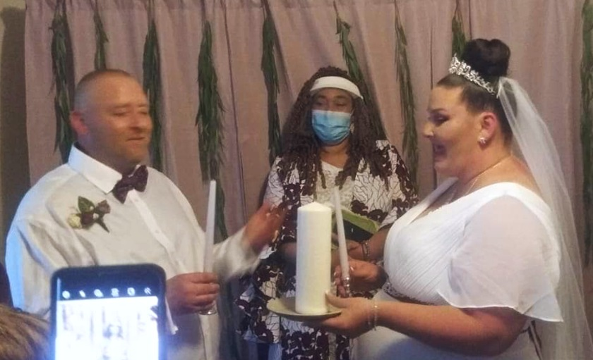 The couple prepares to light the unity candle while the officiant looks on