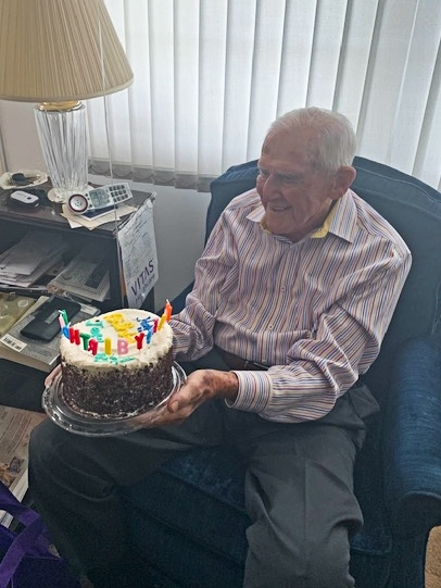 Jerry holds his birthday cake, complete with candles that spell out Happy Birthday