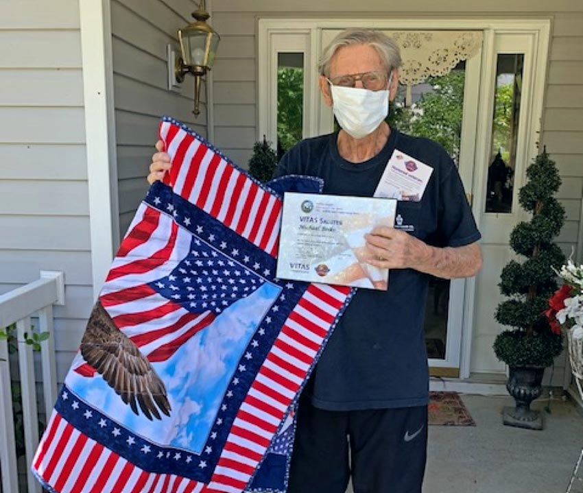 Michael Boiko holds his certificate and quilt on the front porch