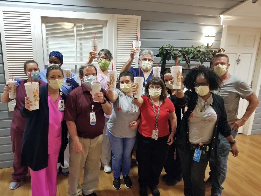 The staff at The Town Square, Steward assisted living facility hold up smoothies provided by VITAS