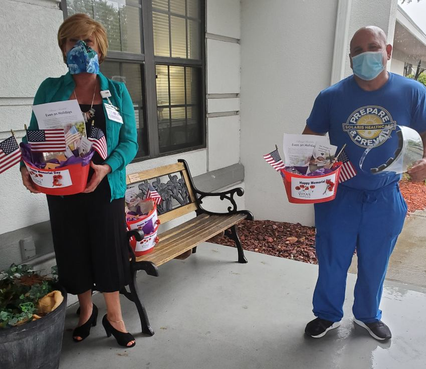 Two people carry Memorial Day baskets into the building