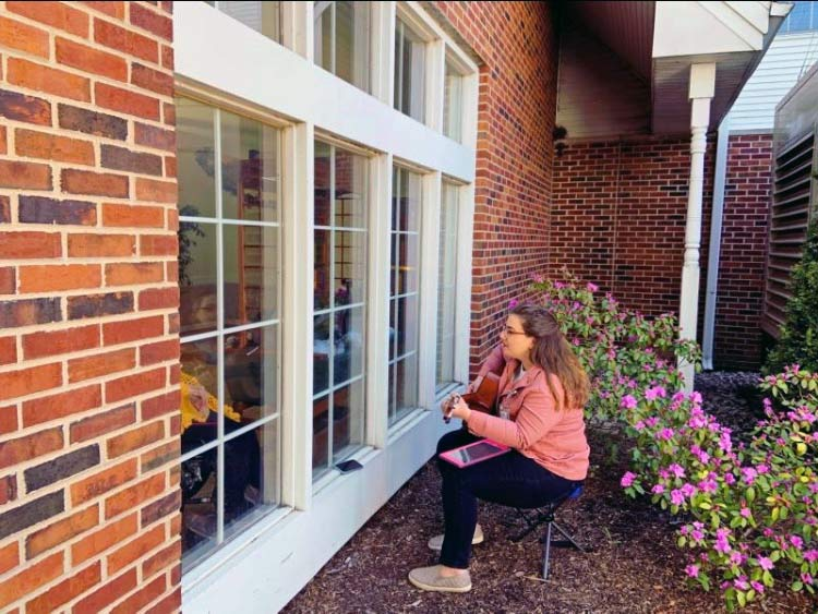 Mia plays outside a window for a patient listening by phone inside