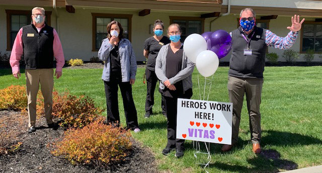 The Kansas City team, wearing masks, cheer on workers at a healthcare facility with balloons, smiles and waves