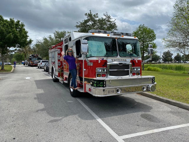 A VITAS team member with a fire truck for the parade