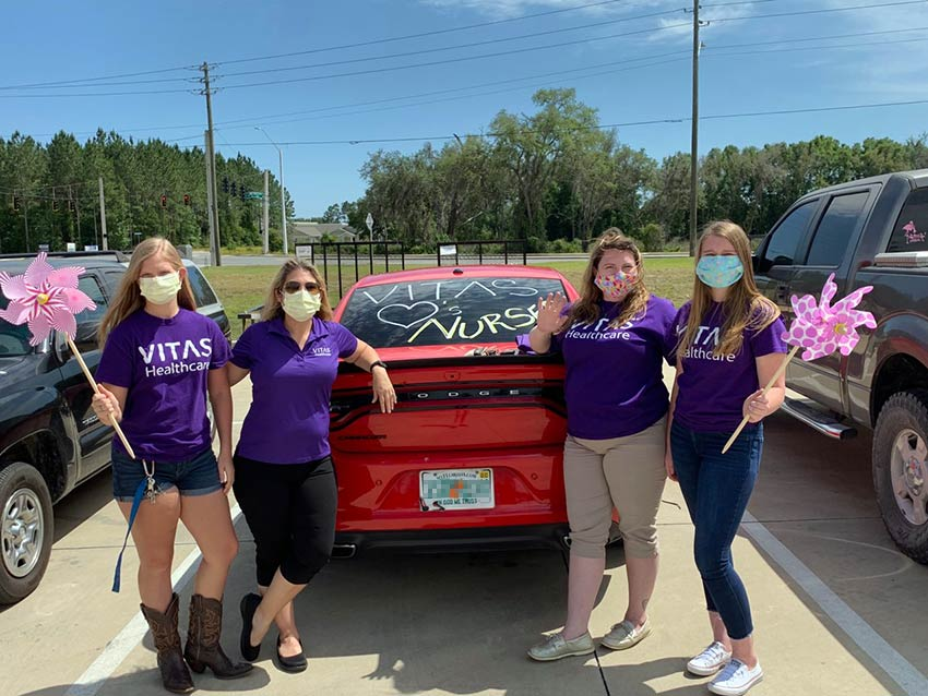 "Four VITAS team members, wearing masks, hold giant pinwheels as they pose behind a Dodge Charger with ""VITAS hearts Nurses"" on its rear window"