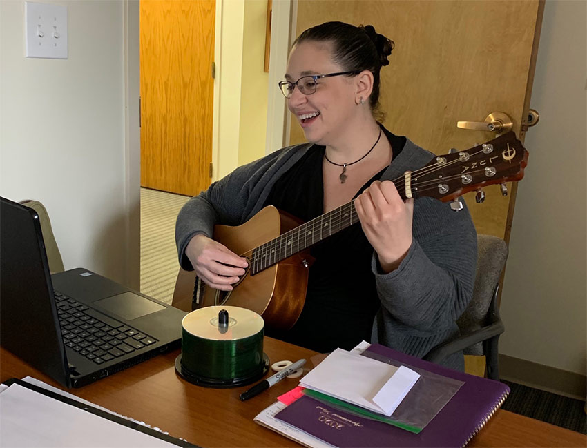 Cheryl Lynn Olson plays guitar and records music at a laptop