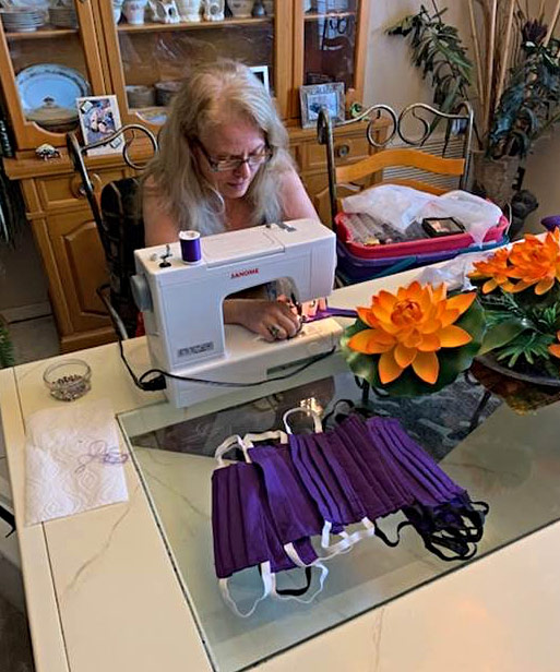 Susan Acocella works at her sewing machine at home