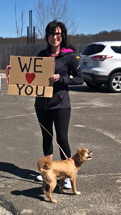 "VITAS Representative Lisa Gould holds her dog's leash and a sign saying ""We Love You"" outside an assisted living facility"