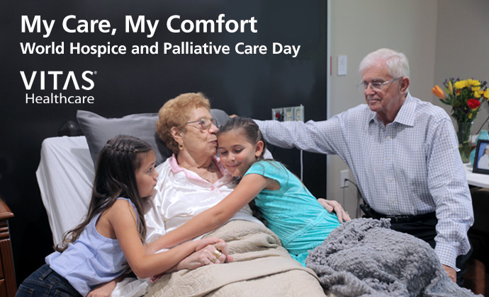 "A woman in bed embraces her two granddaughters as her husband looks on, with the words ""My Care, My Comfort: World Hospice and Palliative Care Day"" on the image"