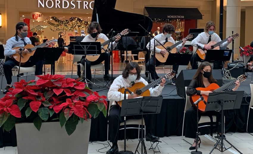A group of young guitarists performs