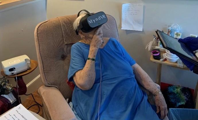 Mary Jean坐在扶手椅中,頭上戴著VR耳機
