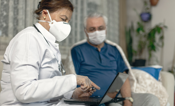 A healthcare professional wearing a protective mask and gloves explains medical information to a hospice patient at home