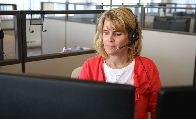 A VITAS team member answers a call at her workstation