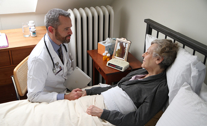 A physician talks to a patient at her bedside