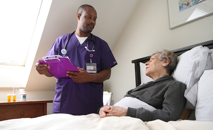 A VITAS nurse talks with a patient as she sits up in bed