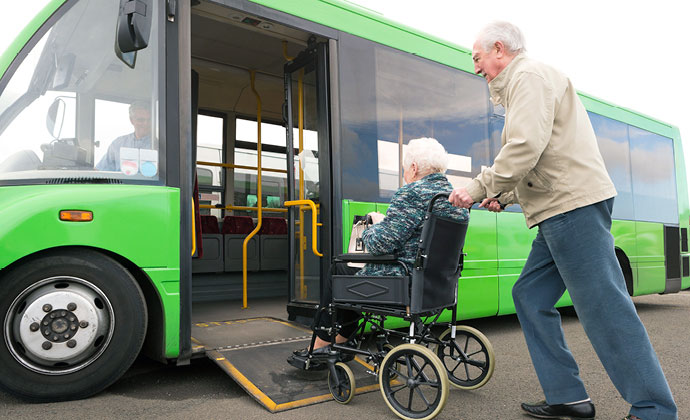 Tinutulungan ng isang lalaking tagapag-alaga ang isang babaeng pasyenteng nasa wheelchair na makasakay sa shuttle