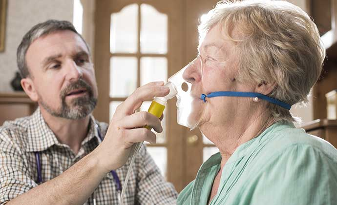 A respiratory therapist helps a patient with an oxygen mask