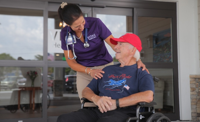 A VITAS clinician talks with a veteran patient who is using a wheelchair outside