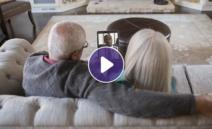 Một cặp đôi cao niên trò chuyện với bác sĩ qua iPad từ ghế sofa tại nhà của họ