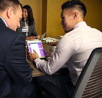 Maraming mga propesyonal sa pangangalagang pangkalusugan na nakaupo sa isang conference table at nakatingin sa isang tablet