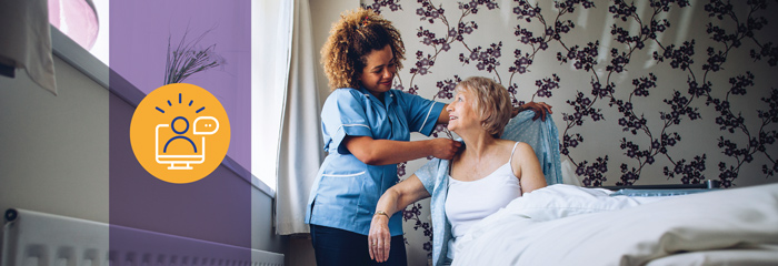 A hospice aide helps a patient put on a shirt