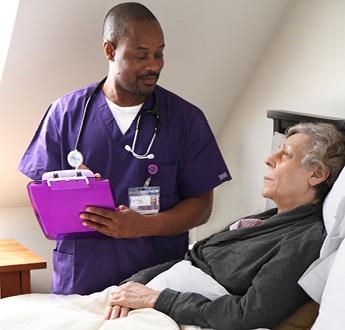 A VITAS provider stands next to a bed, talking to a patient
