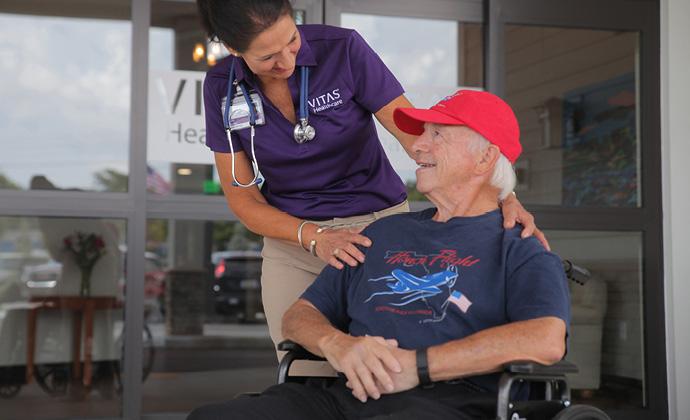 Nakikipag-usap ang isang VITAS providersa isang pasyenteng nakaupo sa wheelchair sa labas