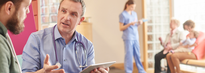 Doctor having conversation holding clipboard