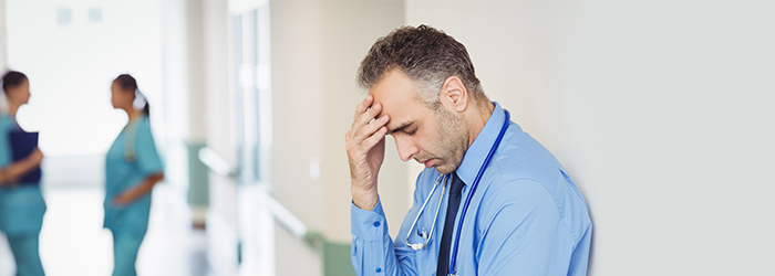 Doctor leaning against wall rubbing forehead