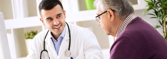 Male doctor smiles at man with glasses