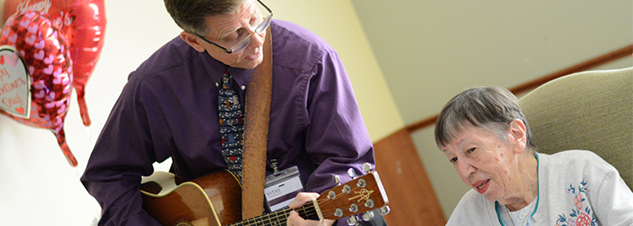 VITAS caretaker playing guitar for hospice patient