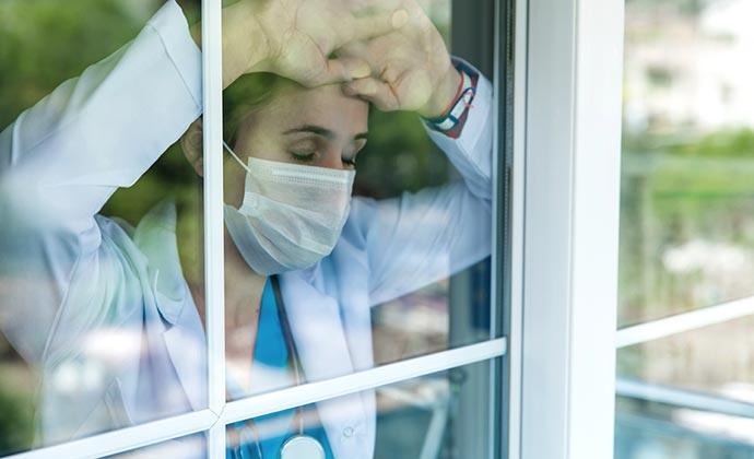 Una trabajadora de asistencia médica agotada, usando el EPP, mira por una ventana