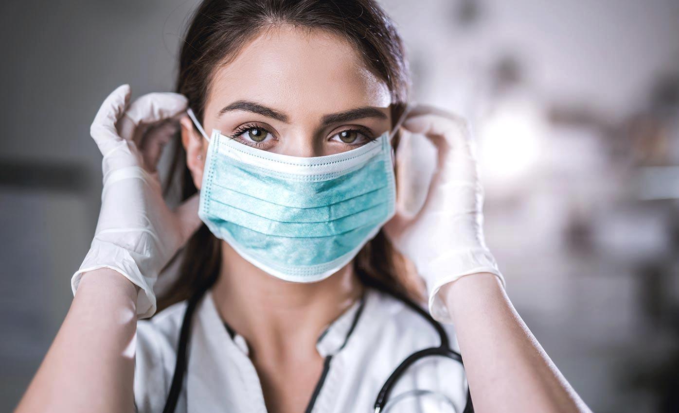 穿著個人防護裝置的臨床醫事人員,臉上也戴著口罩