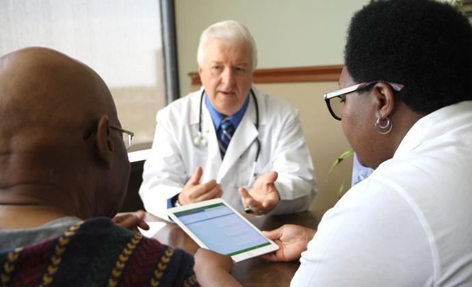 Nakikipag-usapang isang doctorsa isang mag-asawa sa kanyang opisina, habang nakitingin sila sa impormasyon sa isang iPad