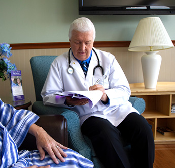A physician talks with a patient in an office
