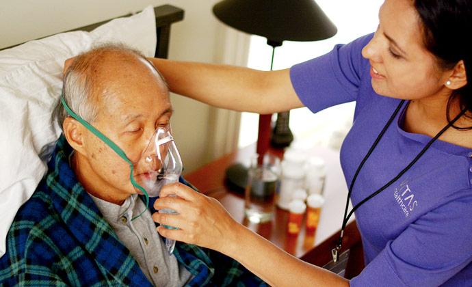 Tinutulungan ng isang nurse ng VITAS ang isang pasyente na isuot ang kanyang oxygen mask