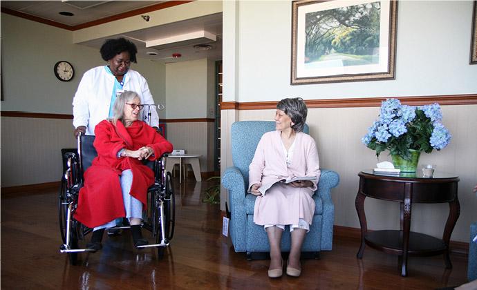 Tinutulungan ng isang nurse ang isang pasyenteng nakaupo sa wheelchair habang nakikipag-usap siya sa isa pang residente
